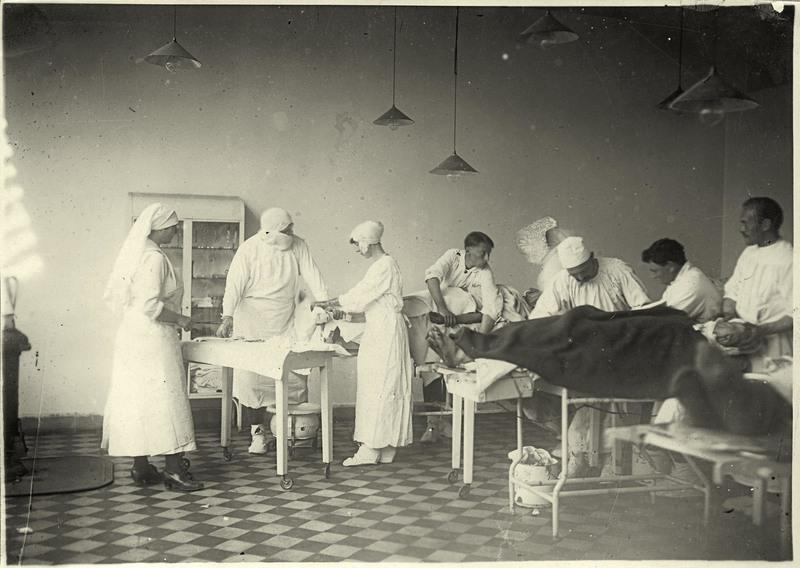 La reine Elisabeth et l'infirmière Henriette van Acke assistent le Dr Antoine Depage pendant une opération