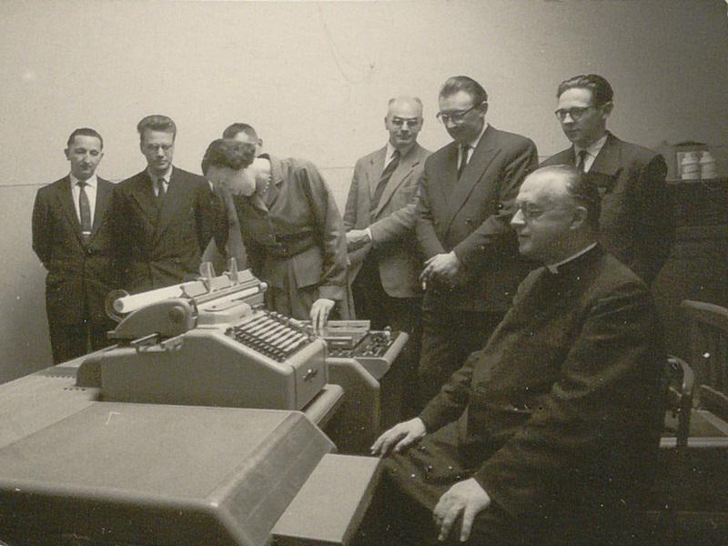 Georges Lemaître devant la Burroughs E101 à l'occasion d'une démonstration au Laboratoire de recherches numériques